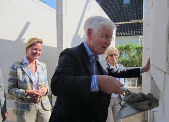 """Dr. Henning Voscherau mauert den Grundstein ein. Im Hintergrund sind links Johanna Stengel, Vorsitzende der Stiftung """"Ein Platz für Kinder"""", und Dorothea Urban (rechts) zu sehen."""